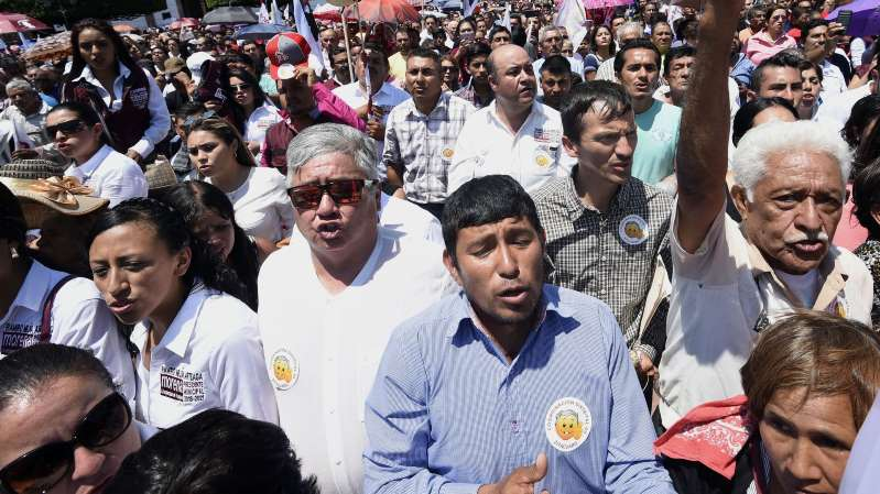 a group of people standing in front of a crowd: Supporters of Mexican presidential candidate Andrés Manuel López Obrador at a campaign rally in Zitacuaro, Michoacan state, Mexico, on May 28.