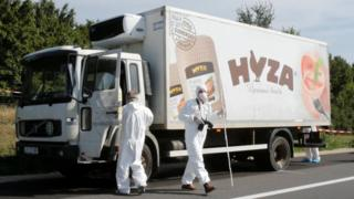 Forensic police officers inspect a parked truck in which migrants were found dead, on a motorway near Parndorf, Austria August 27, 2015