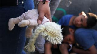 Woman holds doll at US-Mexico border, children resting behind her