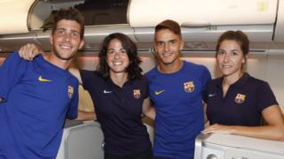 Two male and two female team members are photographed smiling together in the plane's business class