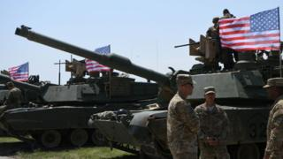 US soldiers stand by Abrams Battle Tanks bearing the US flag prior to the opening ceremony of the joint multinational military exercise