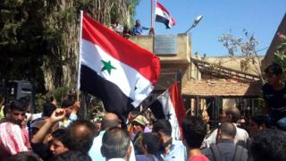 Syrian men wave the national flag in the previously rebel-held town of Tafas, in the Deraa countryside (12 July 2018)