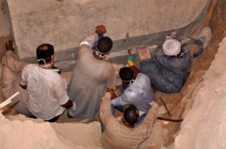 A photo from the Egyptian Ministry of Antiquities shows workers preparing to open the black granite sarcophagus