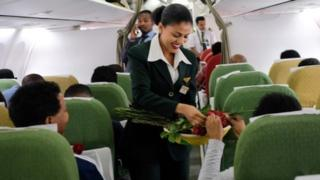 Passengers are welcomed by cabin crew inside an Ethiopian Airlines flight who departed from the Bole International Airport in Addis Ababa, Ethiopia, to Eritrea