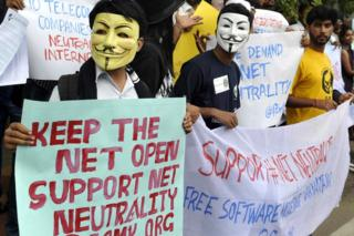 Indian activists wear masks as they hold placards during a demonstration supporting 'net neutrality' in Bangalore