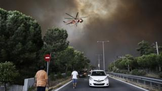 A firefighting helicopter flies over an avenue during a forest fire in Neo Voutsa, a northeast suburb of Athens, Greece, 23 July 2018