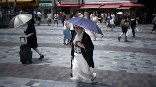 A woman holds an umbrella as she walks along a street in Tokyo on July 23, 2018, as Japan suffers from a heatwave