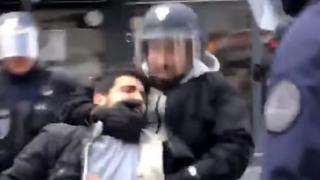 A pixelated image shows a bearded man wearing a hoodie and a riot police helmet grabbing a protester by the neck