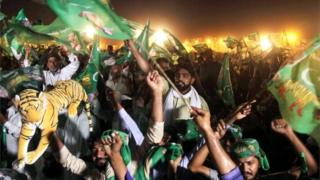 Pakistan Muslim League-Nawaz (PML-N), chant slogans and wave flags during a campaign meeting ahead of the general election in Multan on July 22, 2018.