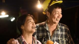 Family members celebrate while camping out near Than Luang cave following news all members of children