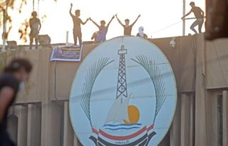Protesters stand on top of an official building in Basra, 6 September 2018