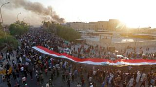Iraqi protesters carry a giant Iraqi flag in Basra, 6 September 2018
