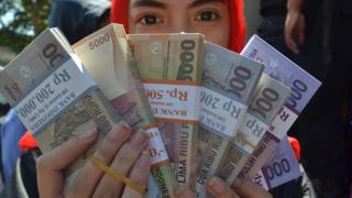 An Indonesian woman holds rupiah notes in 2016