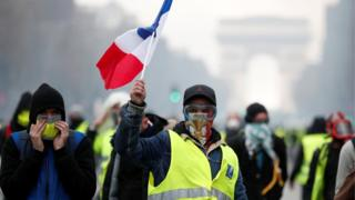Masked protesters wearing yellow vests, a symbol of a French drivers