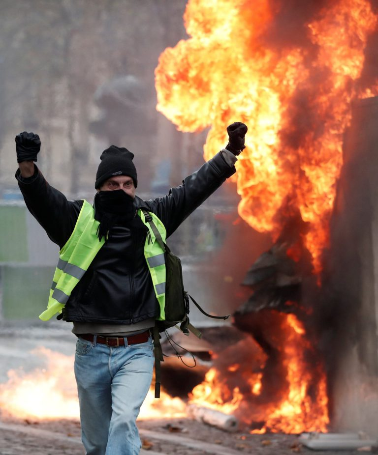A protester wearing yellow vest, a symbol of a French drivers' protest against higher fuel prices, gestures during riots on the Champs-Elysees in Paris, France, November 24, 2018. REUTERS/Benoit Tessier