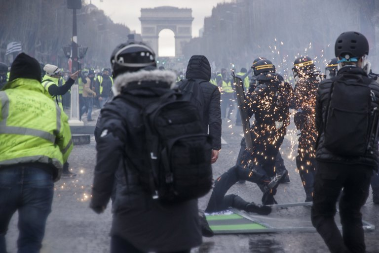 epa07186163 People wearing yellow vests as a symbol of French driver's and citizen's protest against higher fuel prices, clash with the police forces during a demonstration on the Champs Elysee as part of a nationwide protest in Paris, France, 24 November 2018. The so-called 'gilets jaunes' (yellow vests) protest movement, which has reportedly no political affiliation, is protesting over fuel prices. EPA/CHRISTOPHE PETIT TESSON