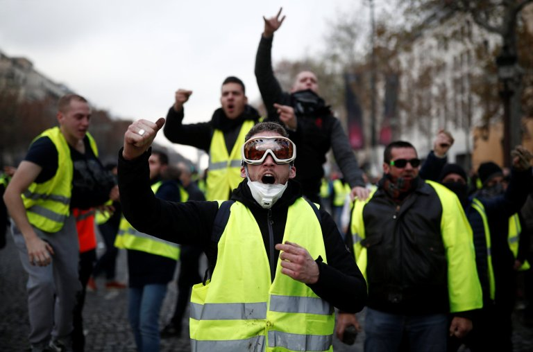 Protesters wearing yellow vest, a symbol of a French drivers' protest against higher fuel prices, shout out slogans on the Champs-Elysee in Paris, France, November 24, 2018. REUTERS/Benoit Tessier