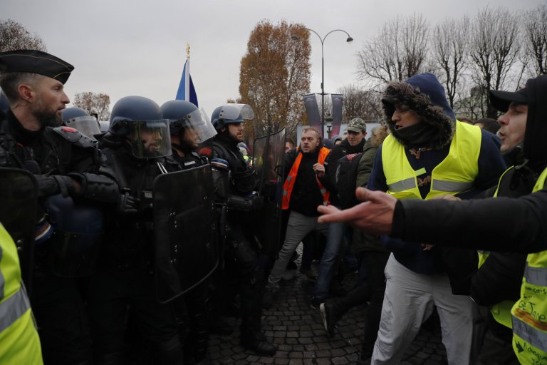 epa07186025 Police forces stop people wearing yellow vests, as a symbol of French driver's and citizen's protest against higher fuel prices, during a demonstration on the Champs Elysee as part of a nationwide protest in Paris, France, 24 November 2018. The so-called 'gilets jaunes' (yellow vests) protest movement, which has reportedly no political affiliation, is protesting over fuel prices. EPA/CHRISTOPHE PETIT TESSON