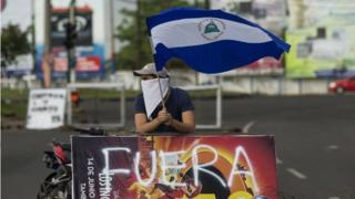 A young man raises the national flag of Nicaragua during a protest in support of the city of Masaya in Managua, Nicaragua, 04 June 2018.