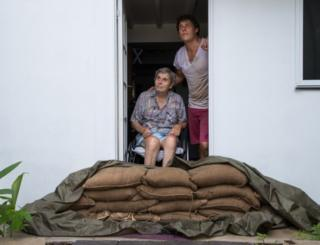 Parramatta Park resident John Irving and his son Steve look at the sky from their sandbagged doorway in Cairns, Queensland, on 15 December 2018.