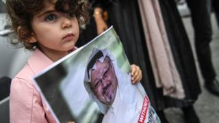 A child holds a picture of the missing journalist