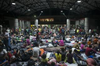 Migrants rest in the main square in Tapachula