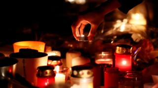 People light candles in tribute to the victims of the deadly shooting in Strasbourg, France, December 13, 2018.