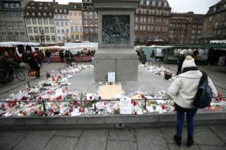 People look at candles, letters and flowers at the Christmas Market in Strasbourg on 14 December 2018