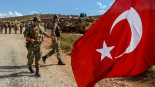 Turkish soldiers stand near armoured vehicles as a man waves a Turkish national flag during a demonstration in support of the Turkish army's Idlib operation near the Turkey-Syria border near Reyhanli, Hatay, on 10 October 2017