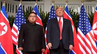 US President Donald Trump (R) poses with North Korea's leader Kim Jong Un (L) at the start of their historic US-North Korea summit