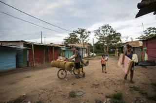 Gael and Olivia carry their belongings back to their shelter