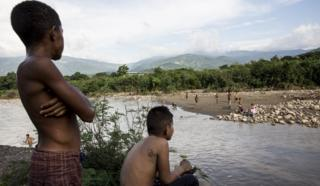 Children play in the river at the border of Columbia and Venezuela