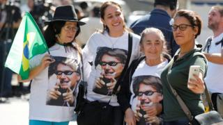 Supporters of Jair Bolsonaro gathered in front of Albert Einstein hospital in Sao Paolo, wearing t-shirts with his face printed on it