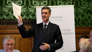 Jacob Rees-Mogg holding the report