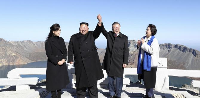 Kim Jong-un, Moon Jae-in join hands on peak of sacred North Korean volcano