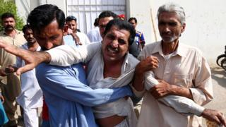 People console an unidentified relative of one of the victims of the attack on Chinese consulate