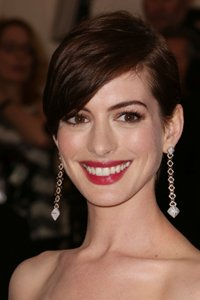 Anne Hathaway has grown out her short layers into a sweeping side fringe that looks chic and elegant.