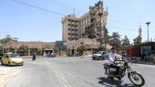 A man rides a motorcycle along a street past the damaged former Carlton Hotel building that serves as a Syrian Red Crescent hospital, in the rebel-held northern Syrian city of Idlib