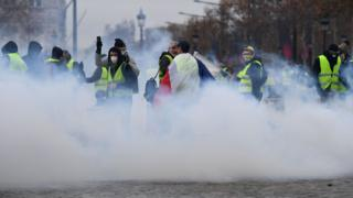 Protesters stand in smoke from police grenades in Paris on 1 December 2018