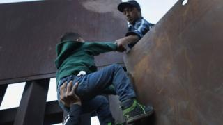 A boy is hoisted by fellow members of the migrant caravan over the US-Mexico border fence
