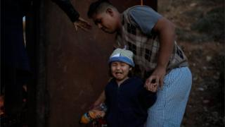 A migrant girl from Honduras cries as a group of migrants tries to jump a border fence to cross illegally from Mexico to the US on 2 December, 2018